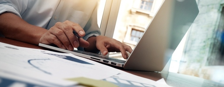 business documents on office table with smart phone and digital tablet and graph financial diagram and man working in the background-672383-edited.jpeg